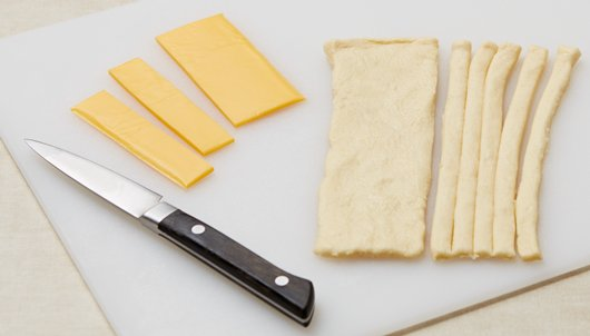 With knife or kitchen scissors, cut each rectangle lengthwise into 10 pieces, making a total of 40 pieces of dough. Slice cheese slices into quarters (1/2 slice cheese, cut in half).